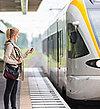 Eine Frau wartet am Gleis auf ihren Zug